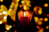 two hands illuminated by  a candle in the darkness