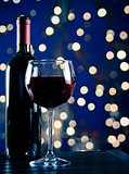 red wine glass near bottle with light blue bokeh