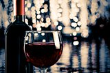 red wine glass near bottle with light bokeh