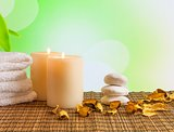 Spa massage border background with towel stacked, candles and perfumed leaves