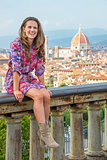 Smiling young woman sitting against panoramic view of florence,