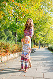 Portrait of happy mother and baby girl walking in city park