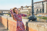 Smiling young woman on embankment near ponte vecchio in florence