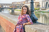 Portrait of happy young woman on embankment near ponte vecchio i