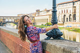 Happy young woman on embankment near ponte vecchio in florence,