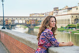 Thoughtful young woman on embankment near ponte vecchio in flore