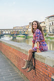 Happy young woman sitting near ponte vecchio in florence, italy
