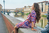 Relaxed young woman sitting near ponte vecchio in florence, ital