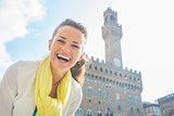 Happy young woman in front of palazzo vecchio in florence, italy