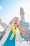 Happy young woman showing victory gesture in front of palazzo ve