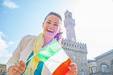 Happy young woman showing flag in front of palazzo vecchio in fl