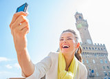 Happy young woman making selfie in front of palazzo vecchio in f