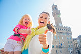 Happy mother and baby girl showing thumbs up in front of palazzo