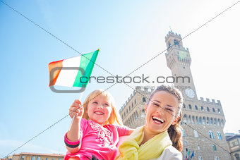 Portrait of happy mother and baby girl with flag in front of pal