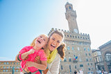 Portrait of happy mother and baby girl in front of palazzo vecch