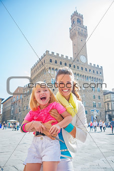 Portrait of smiling mother and baby girl in front of palazzo vec