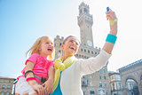Happy mother and baby girl making selfie in front of palazzo vec