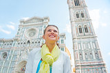 Happy young woman looking into distance in front of duomo in flo