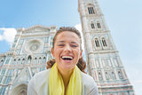 Portrait of happy young woman in front of duomo in florence, ita