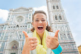 Happy young woman showing thumbs up in front of duomo in florenc