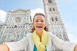 Smiling young woman making selfie in front of duomo in florence,