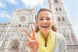 Happy young woman showing victory gesture in front of duomo in f