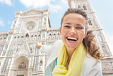 Happy young woman pointing on duomo in florence, italy