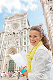 Happy young woman with map near duomo in florence, italy