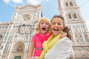 Portrait of happy mother and baby girl in front of duomo in flor