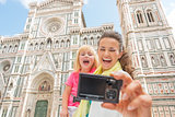 Smiling mother and baby girl making selfie in front of duomo in