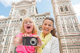 Happy mother and baby girl taking photo in front of duomo in flo