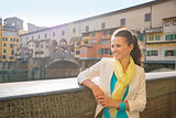 Happy young woman looking into distance near ponte vecchio in fl