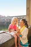 Happy mother and baby girl eating ice cream near ponte vecchio i