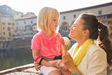 Happy mother and baby girl eating ice cream near ponte vecchio i