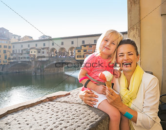 Portrait of happy mother and baby girl eating ice cream near pon