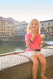 Portrait of happy baby girl eating ice cream near ponte vecchio