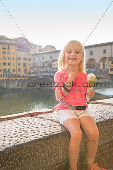 Portrait of happy baby girl eating ice cream near ponte vecchio