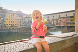 Happy baby girl eating ice cream near ponte vecchio in florence,