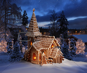 Gingerbread church on snowy Christmas night landscape
