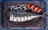 Salted mackerel with vegetables on a plate, top view