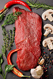 raw beef steak with spices and herbs