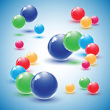 Different colour glass balls on blue background.