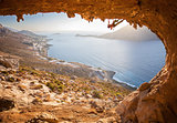 Male rock climber climbing along a roof in a cave. Kalymnos island, Greece.
