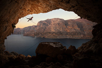 Female rock climber falling of a cliff in a big cave at Kalymnos, Greece