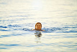 smiling girl swims in the sea at dawn