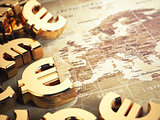 Euro sign on the world map background with DOF effect.