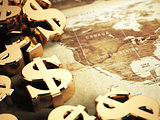 Dollar sign on the world map background with DOF effect.