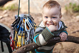 Child of rock climbers smiling while standing next to bundle of quickdraws
