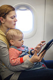 Caucasian mother and toddler son using tablet pc during while on board of airplane