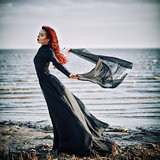 Beautiful sad goth girl with cloth in hands standing on sea shore
